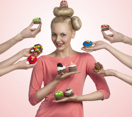 pretty blonde girl with colored make-up and funny hair-style taking cupcakes photo