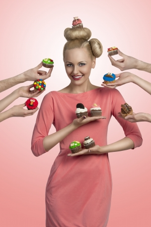 smiling blonde girl with one cupcake on the head, surrounded by some hands with colorful cupcakes photo