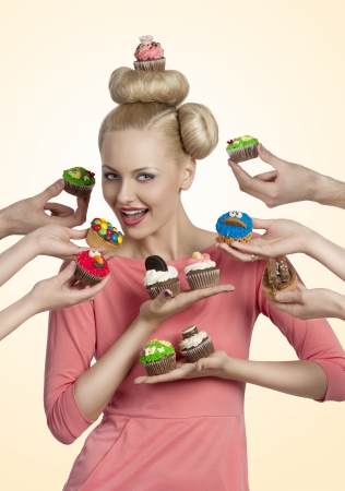 beauty blonde woman with cupcake on the head, some hands tendering other colorful cupcakes near her face photo