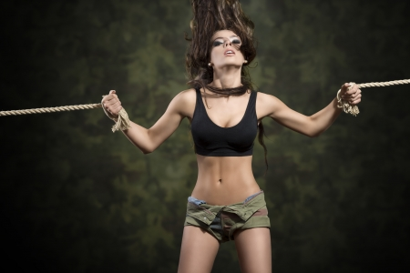 strong sensual brunette girl tied by rope with flying hair and sexy top and shorts   photo