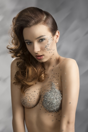 sexy bared woman with elegant hair-style and creative make-up with some bright decorations on the face and on the breast