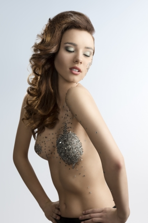 nude pretty girl: cute young girl with fashion hair-style and creative make-up  Some bright decorations on her face and naked body  Stock Photo