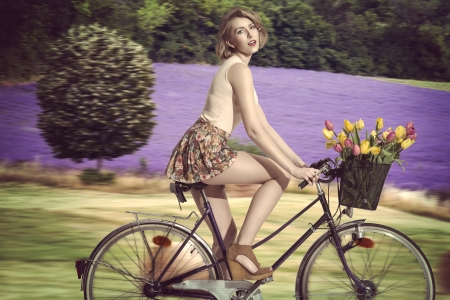 lavander: pretty blonde woman going  on the bicycle with colourful flowers in the basket. She wearing pink tank and very short floral skirt. rural field lavander