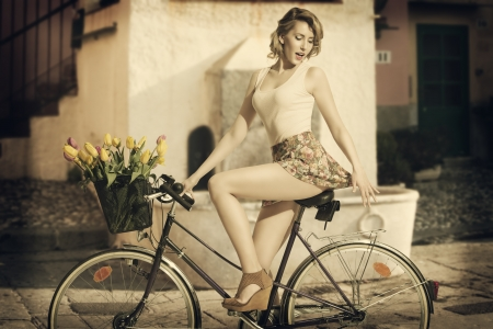 sensual blonde girl  on the bicycle with pink tank and short floral skirt. She covering her backside with hand. Some colourful flowers in the bike's basket  photo