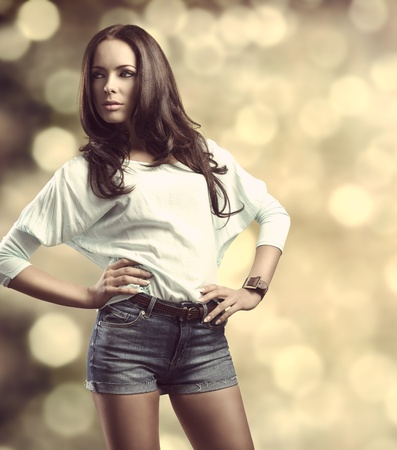 portrait of fashionable brunette girl with smooth hair, casual clothes and denim shorts in fashion pose in bokeh background photo