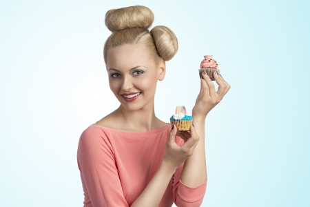 portrait of pretty young girl with funny hair-style and colourful make-up taking two cupcakes in the hands and smiling photo