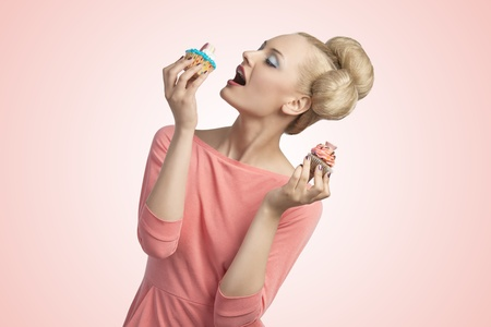 pretty blonde woman with creative hair-style and colourful make-up eating cupcakes and wearing pink dress Stock Photo - 20704316