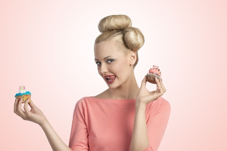 pretty blonde girl with creative hair-style and colourful make-up taking two sweets cupcakes and looking in camera  photo