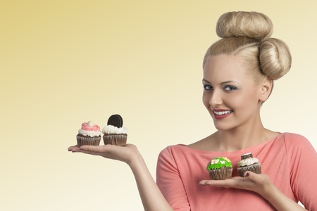 pretty young blonde woman with creative hair-style and colourful make-up showing variety of sweets cupcakes   photo