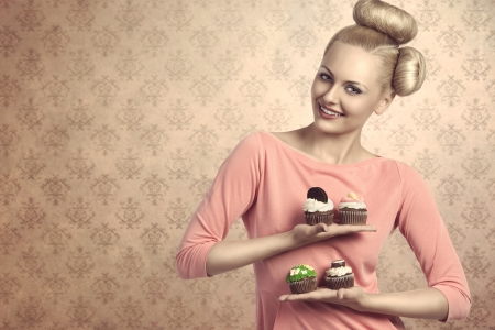 beautiful blonde girl with creative hair-style and colourful make-up taking four  variety of sweets cupcakes  in the hands photo