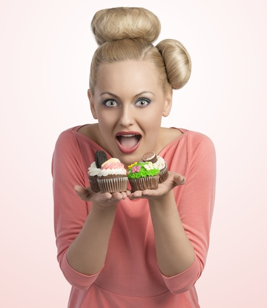 portrait of funny girl with creative hair-style and colourful make-up offering some cupcakes with the hands  photo