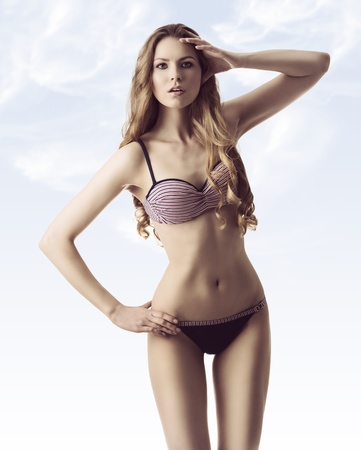 attractive gorgeous: beauty blonde girl with long wavy blonde hair and stunning body in fashion pose wearing bikini