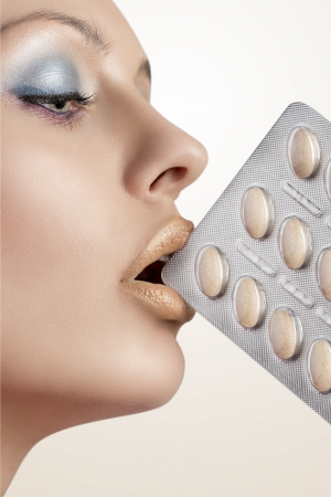 close-up portrait of girl with colourful make-up and perfect skin taking blister of pills between her lips  photo