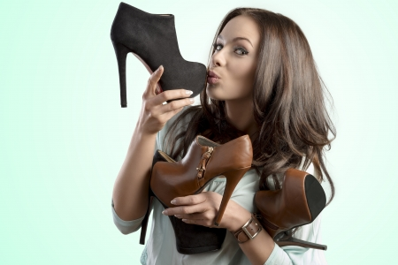 funny portrait of pretty brunette girl with many heels in her hands in the sales season. She kissing one shoes