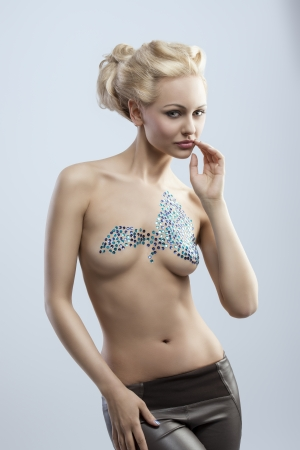 splendid blonde woman with creative hair-style shows her nude body with bright decorations on breast