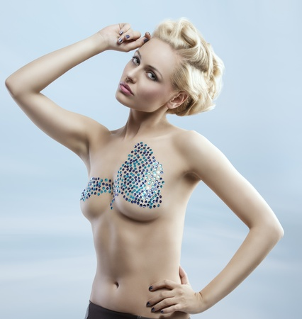 nude woman posing: splendid fashion girl with blonde elegant hair-style posing and shows glitter decorations on her nude breast  Stock Photo