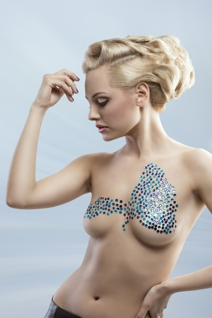 beauty breast: sexy fashion lady with blonde elegant hairdo posing with  creative glossy decoration on her nude breast