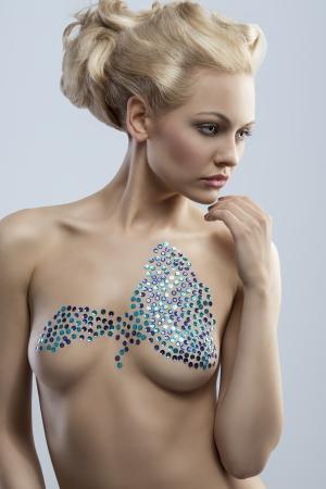 verbazingwekkende blonde vrouw met creatieve blond haar-stijl poseren en toont haar naakt borst met glanzende versiering op de huid