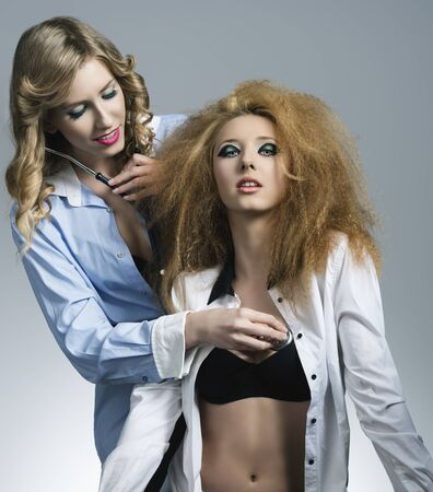 couple sensual blonde girls in fashion portrait posing with open shirt, stethoscope and creative hair-style and make-up Stock Photo - 21171339