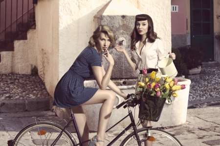 portrait of two sensual vintage style girls with bicycle, colourful flowers in the basket and watering can , in vintage color
