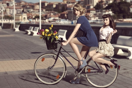couple of fashion women with vintage style on bicycle, colourful tulips in the basket of the bike in vintage color outdoor near the sea photo