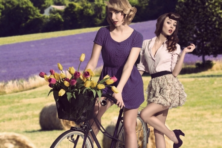 fashion portrait of couple sensual girls with vintage style near bicycle with floral basket  Stock Photo