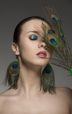 portrait of pretty brunette girl with make-up and accessory inspired by peacock feathers  photo