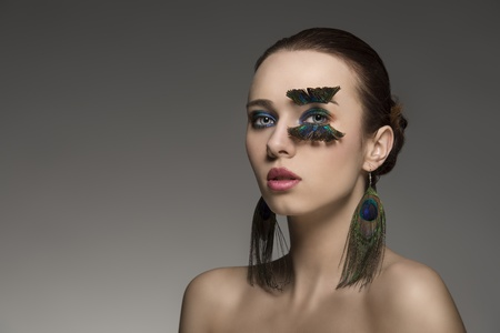 close-up portrait of sexy woman with brown hair and make-up and accessory inspired by peacock feathers  photo