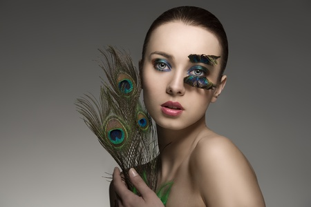 splendid naked brunette woman with make-up and accessory with colored peacock feathers. looking in camera  photo