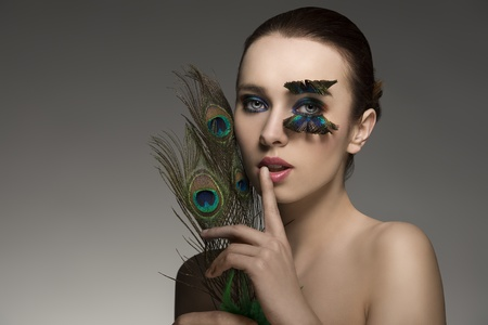 beauty portrait of sensual brunette girl with naked shoulders and elegant make-up and accessory inspired by peacock feather   photo