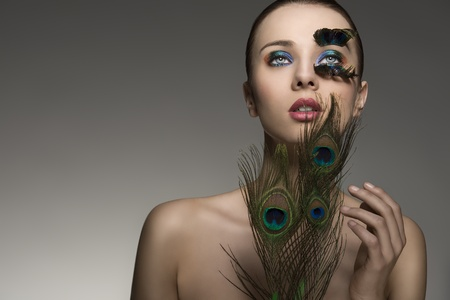 beauty close-up portrait of beautiful brunette lady with naked shoulders and peacock feather in make-up and accessory  photo