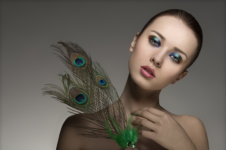 amazing portrait of young girl with perfect skin, naked shoulders, make-up and accessory inspired by peacock's feathers  photo