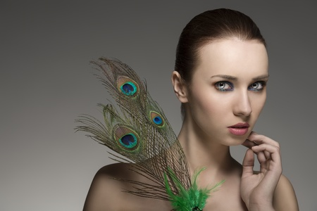 close-up beauty portrait of sexy female with brown hair-style posing with elegant make-up and accessory inspired by peacock's feather   photo