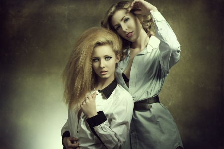 hot portrait of couple blonde girls with creative style, cute make-u,  hairdo and open shirt in fashion pose  photo