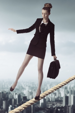unstable: full-length portrait of blonde business woman with dark suit and working bag in unstable balance