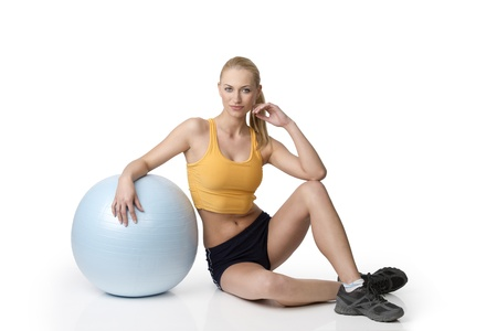 gym dress: fitness girl in gym dress sitting on white with a ball near her . natural skin Stock Photo