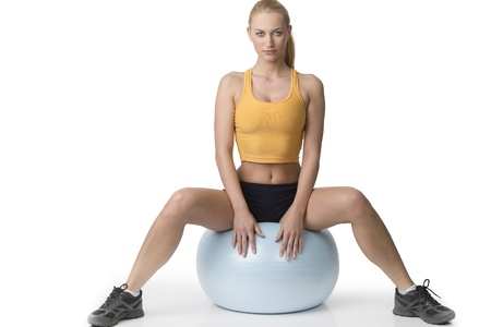 sitting down: very stunning young pretty woman with gym body , sitting down on a fitness ball