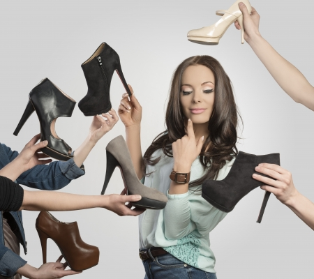 sexy brunette girl in shopping time posing surrounded by assortment of shoes. Looking shoes and smiling   photo