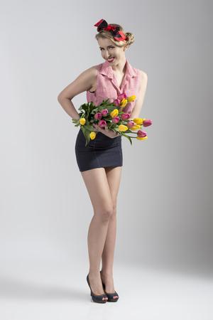 falda corta: retrato de cuerpo entero de la rubia sexy pin-up con flores de colores en las manos. Ella llevaba falda corta y tacones Foto de archivo