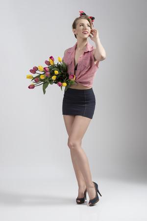falda corta: mujer rubia que llevaba como pin-up con falda corta y camisa abierta posando retrato de cuerpo entero y tomando flores de colores en las manos