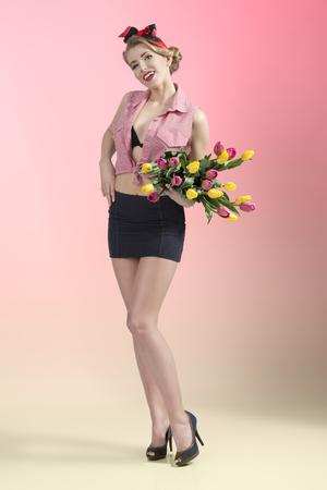 falda corta: sexy rubia mujer pin-up posando con colorido ramo de tulipanes y vistiendo falda corta, camisa abierta y el sujetador negro. Retrato de cuerpo entero