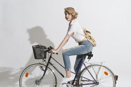 portrait of casual blonde woman with jeans, white shirt and small backpack on a bicycle    photo