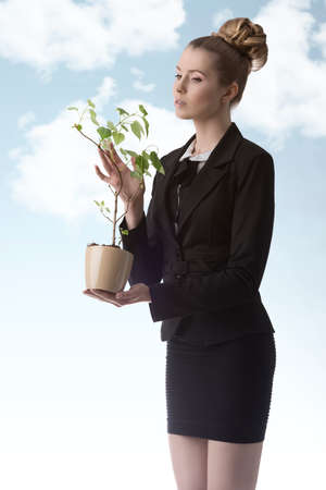portrait of pretty businesswoman with blonde hair-style and elegant suit taking rich money plant in the hands photo
