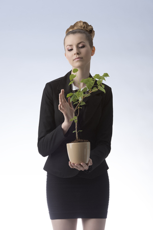 elegant successful business woman with blonde hair style wearing dark suit holding rich money plant  photo