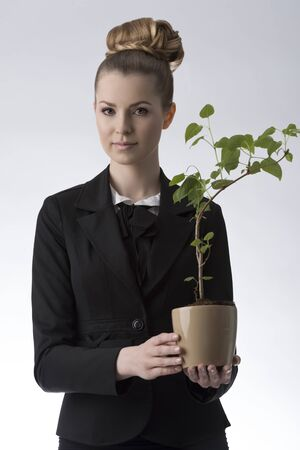 portrait of pretty business woman with successful look and blonde hair-style taking luxuriant money plant in the hand  photo