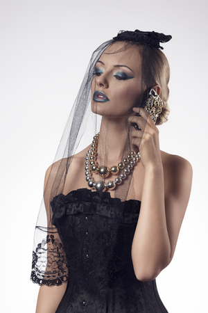 sexy gothic female with bizarre halloween style and make-up talking on the smartphone and wearing dark veil on the face and big necklace  photo