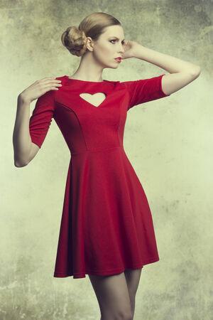 sensual blonde female with creative hair-style and pretty make-up in fashion pose wearing red dress with heart shaped neckline  photo