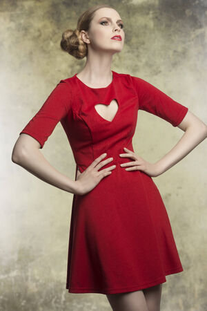 portrait of attractive female with blonde hair-style and elegant make-up in fashion pose wearing red romantic dress with heart shaped neckline  photo