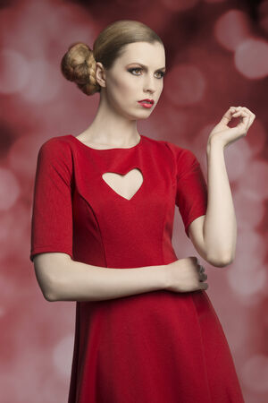 portrait of attractive blonde girl with cute hair-style and make-up posing with romantic style wearing red dress with sexy heart shaped neckline  photo