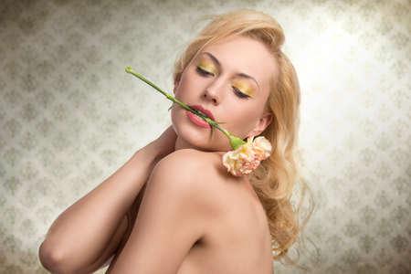 labios sensuales: sexy mujer rubia con los hombros y colorido maquillaje en pose sensual con el clavel entre sus labios Foto de archivo